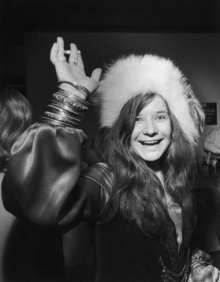 American rock singer Janis Joplin (1943 - 1970) smiles and waves with a cigarette in one hand and a drink in the other  while attending a party. She wears a fur hat.  (Photo by Walter Daran/Hulton Archive/Getty Images)