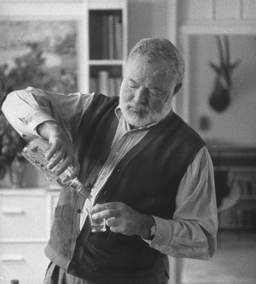 Author Ernest Hemingway pouring himself shot of liquor, at home.  (Photo by Tore Johnson/Pix Inc./Time Life Pictures/Getty Images)