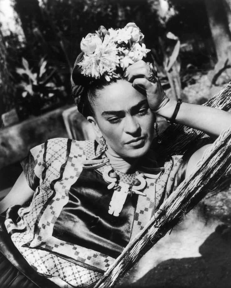 circa 1950:  Mexican artist Frida Kahlo (1907 - 1954), wearing a folk costume and flowers in her hair, leans her head on her hand while lying in a hammock.  (Photo by Hulton Archive/Getty Images)