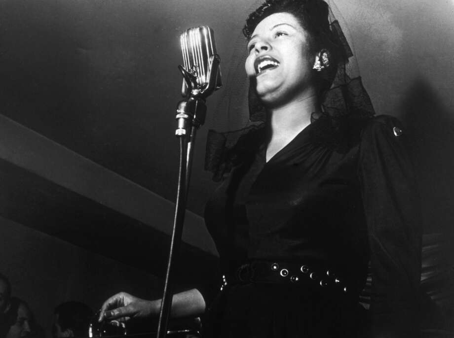 1st February 1942:  American jazz singer Billie Holiday (1915 - 1959) sings in front of a microphone at a Sunday afternoon jam session at Ryan's on 52nd Street, New York City.  (Photo by Charles Peterson/Hulton Archive/Getty Images)