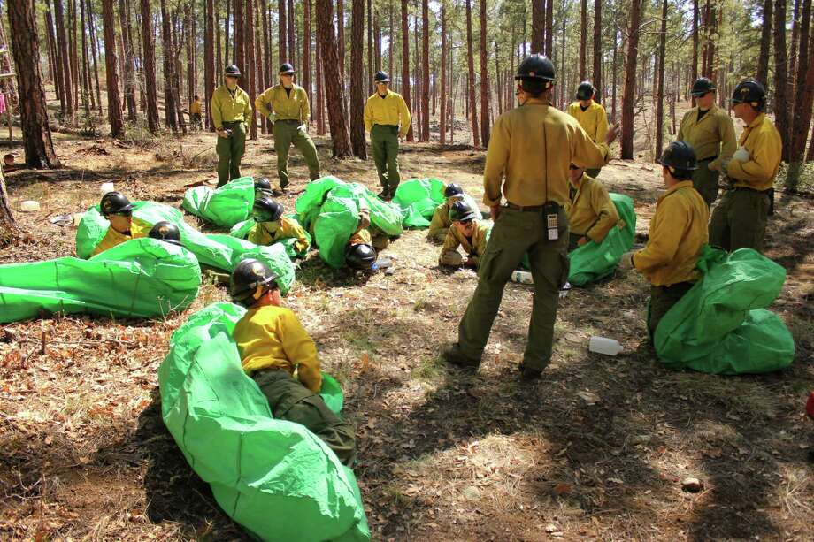 In this April 12, 2012 photo provided by the Cronkite News, Phillip Maldonado, a squad leader with the Granite Mountain Hotshots, trains crew members on setting up emergency fire shelters outside of Prescott, Ariz. On Sunday, June 30, 2013, 19 members of the Prescott-based crew were killed in the deadliest wildfire involving firefighters in the U.S. for at least 30 years. The firefighters were forced to deploy their emergency fire shelters - tent-like structures meant to shield firefighters from flames and heat - when they were caught near the central Arizona town of Yarnell, according to a state forestry spokesman. (AP Photo/Cronkite News, Connor Radnovich) ORG XMIT: AZCR101 Photo: Connor Radnovich / Cronkite News