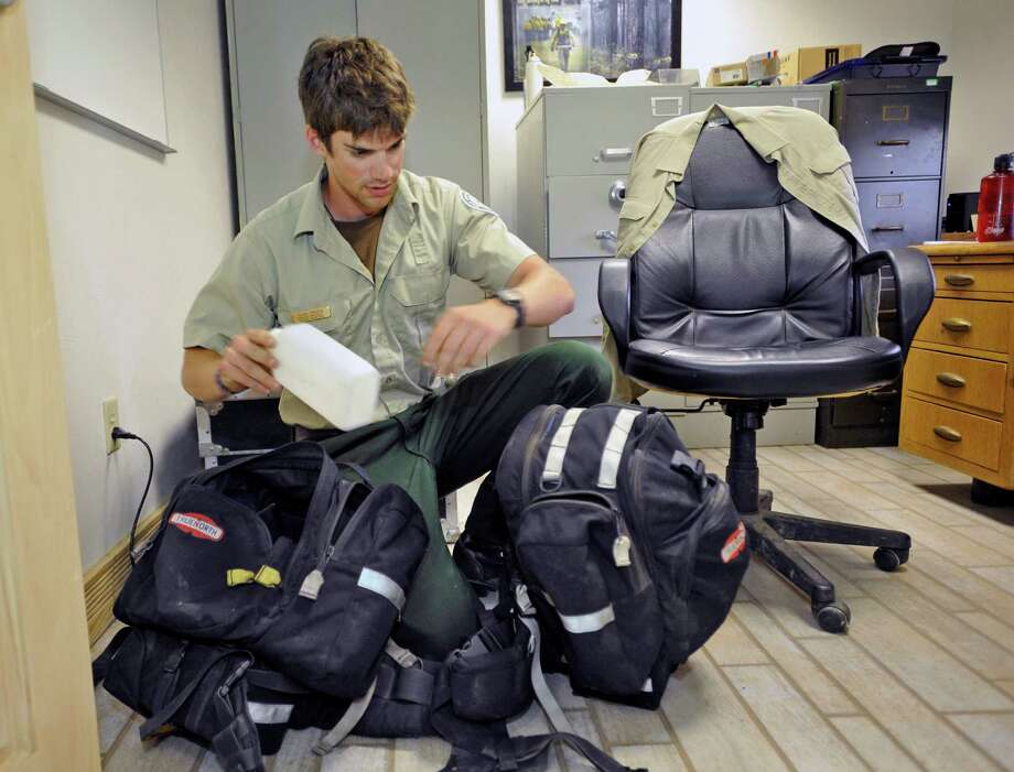 Cash Driggs, a firefighter from the Olive-Woodville district of the Texas A & M Forest Service, leaves Tuesday July 2, 2013, for Arizona to help battle the Yarnell Hill wildfire that killed 19 firefighters from an elite team based in Prescott on Sunday. He was packing gear including several  plastic water bottles and getting up-to-date information Monday at the Olive Headquarters just north of Kountze Texas. This will be his first out of state deployment since joining the state forest service firefighting team in 2012.  Dave Ryan/The Enterprise