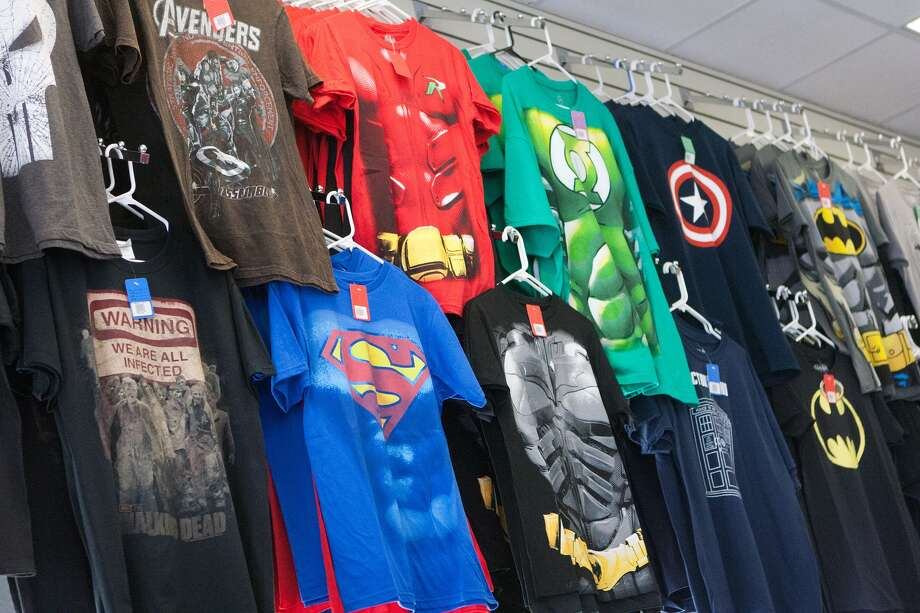 Superhero and comic-themed T-shirts line a wall  at Bedrock City Comics at 4602 Washington Ave. Photo: R. Clayton McKee, Freelance / © R. Clayton McKee