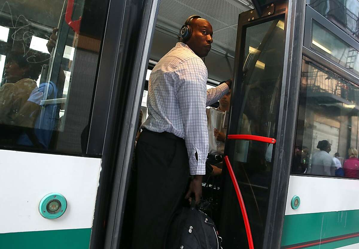 In this file photo, a commuter stands inside an Alameda-Contra Costa (AC) Transit bus in Oakland.