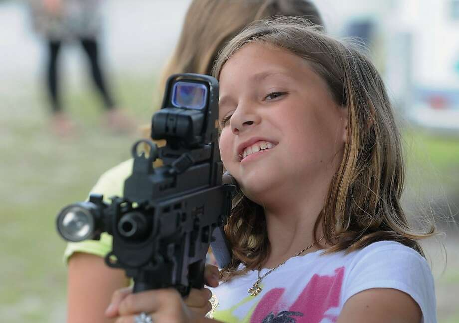 Safety first:At safe summer camp in Castle Hayne, N.C., 9-year-old Holly Burnett looks down the scope of a Heckler & Koch UMP45 submachine gun. Police officers showed the gun during a Gang Resistance Education And Training exercise designed to thwart gang influence in schools. Photo: Mike Spencer, Associated Press