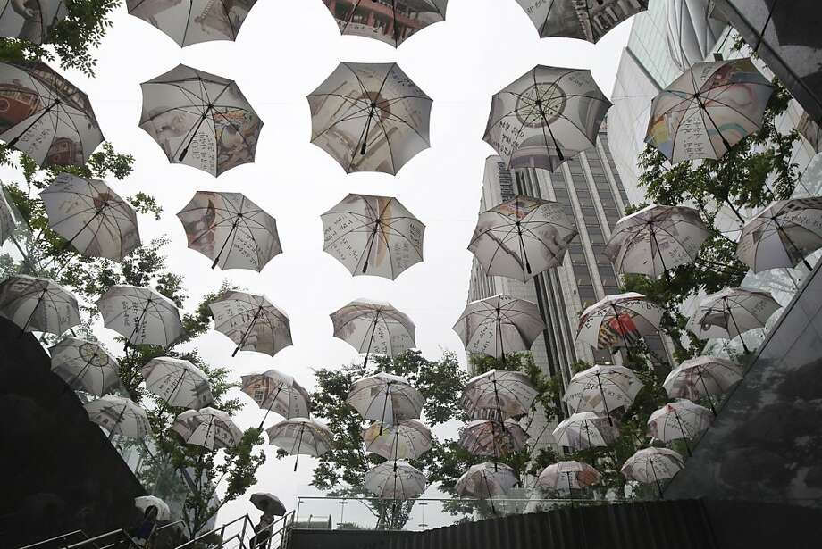 Maximum coverage: Umbrellas hang in front of Seoul City Hall to symbolize Seoul's commitment to protect its citizens. Photo: Ahn Young-joon, Associated Press