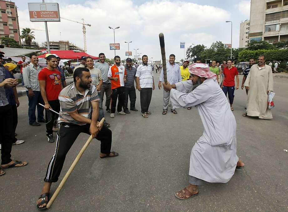 Batter up: Supporters of Egyptian President Mohammed Morsi train with sticks outside Rabia el-Adawiya mosque in Cairo in case any anti-government protests break out. Photo: Amr Nabil, Associated Press