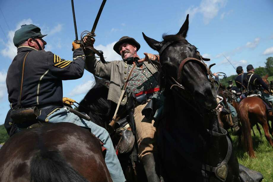 GETTYSBURG, PA - JUNE 29:  Union and Confederate re-enactors skirmish during a re-enactment of the Battle of Gettysburg on June 29, 2013 in Gettysburg, Pennsylvania. Some 8,000 re-enactors are participating in events marking the 150th anniversary of the July 1-3, 1863 Battle of Gettysburg, considered the turning point in favor of the Union in the American Civil War. Union and Confederate armies suffered a combined total of some 46,000-51,0000 casualties in the battle, the highest of any conflict of the war.  (Photo by John Moore/Getty Images) *** BESTPIX *** ORG XMIT: 160017227 Photo: John Moore, Getty / 2013 Getty Images