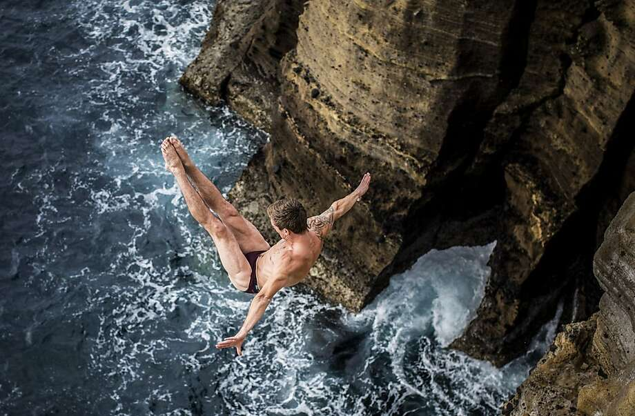 Mat Cowen of the UK dives 27 metres from the cliff face during the first competition day of the third stop of the Red Bull Cliff Diving World Series on June 28, 2013 at Islet Vila Franca do Campo, Azores, Portugal. (Photo by Romina Amato/Red Bull via Getty Images) Photo: Handout, Red Bull Via Getty Images