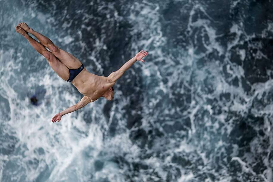 David Colturi of the USA dives 27 metres from the cliff face during the first competition day of the third stop of the Red Bull Cliff Diving World Series on June 28, 2013 at Islet Vila Franca do Campo, Azores, Portugal. (Photo by Dean Treml/Red Bull via Getty Images) Photo: Handout, Red Bull Via Getty Images