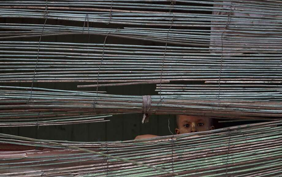 Peek-a-bamboo: A child peers through a screen on a balcony in Aung Mingala, Myanmar's Rakhine state. Photo: Gemunu Amarasinghe, Associated Press