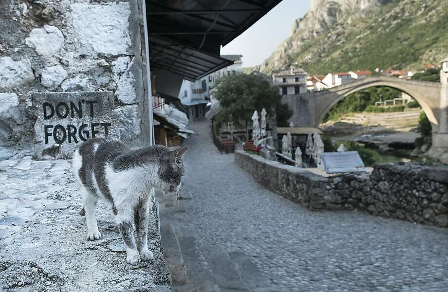 'Don't forget' - to feed me: A sign on the Old Bridge in Mostar, Bosnia and Herzegovina, recalls the 1993 conflict between Croatia and Bosnia. Fighting lasted for 18 months as Bosnia and Herzegovina declared independence from Yugoslavia. Most of Mostar was destroyed. Photo: Marco Secchi, Getty Images
