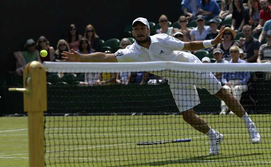 TOPSHOTS Serbia's Viktor Troicki dives for the ball without his racquet after losing grip on his racquet in a previous dive for a return against Russia's Mikhail Youzhny in their third round men's singles match on day six of the 2013 Wimbledon Championships tennis tournament at the All England Club in Wimbledon, southwest London, on June 29, 2013. AFP PHOTO / ADRIAN DENNIS -  RESTRICTED TO EDITORIAL USEADRIAN DENNIS/AFP/Getty Images ORG XMIT: 1878 Photo: ADRIAN DENNIS, Getty / AFP