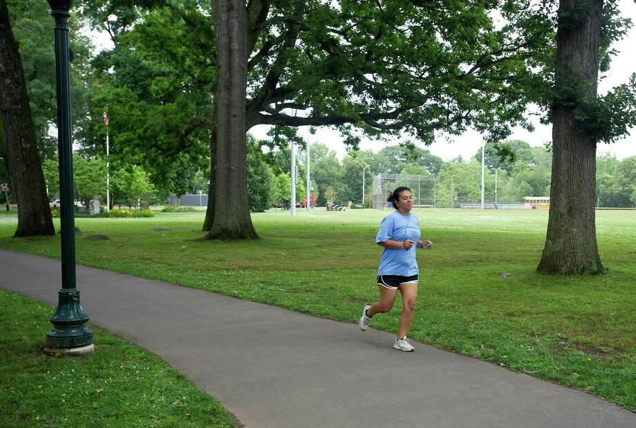 A woman runs in Scalzi Park after the ceremony for the completion of the park's renovation on Tuesday, July 2, 2013. Photo: Lindsay Perry / Stamford Advocate