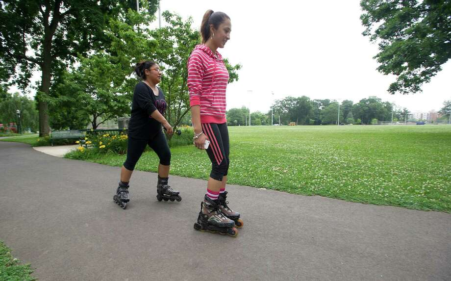 Women in-line skate in Scalzi Park after the ceremony for the completion of the park's renovation on Tuesday, July 2, 2013. Photo: Lindsay Perry / Stamford Advocate