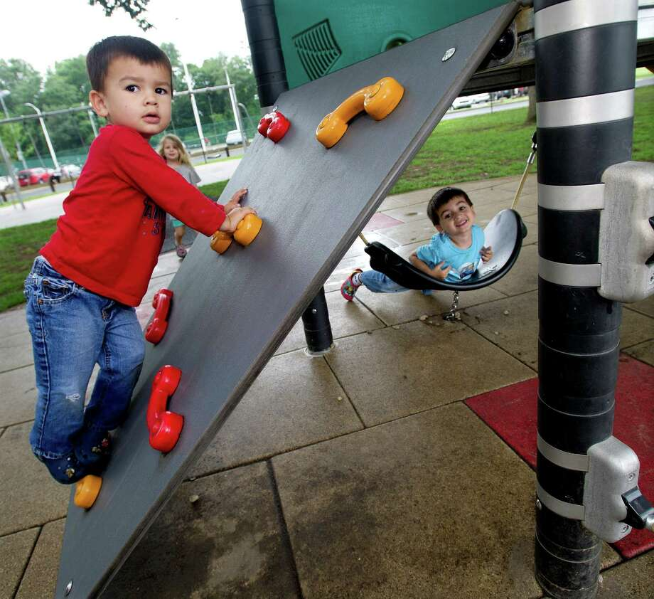 Jake Villanueva, 2, left, and his brother, Max, 3, right, play at Scalzi Park after the ceremony for the completion of the park's renovation on Tuesday, July 2, 2013. Photo: Lindsay Perry / Stamford Advocate