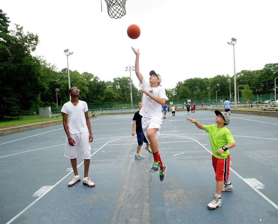Aaron Miller, 14, plays basketball with Pathfinders Adventure Camp at Scalzi Park after the ceremony for the completion of the park's renovation on Tuesday, July 2, 2013. Photo: Lindsay Perry / Stamford Advocate