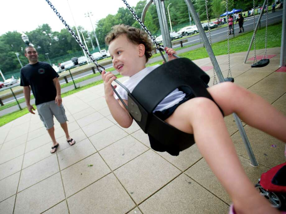 Ella Procaccini, 3, gets a push on a swing from her father, Rob, at Scalzi Park after the ceremony for the completion of the park's renovation on Tuesday, July 2, 2013. Photo: Lindsay Perry / Stamford Advocate