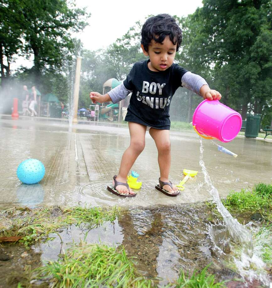 Veer Singh, 2, plays at the splash pad at Scalzi Park after the ceremony for the completion of the park's renovation on Tuesday, July 2, 2013. Photo: Lindsay Perry / Stamford Advocate