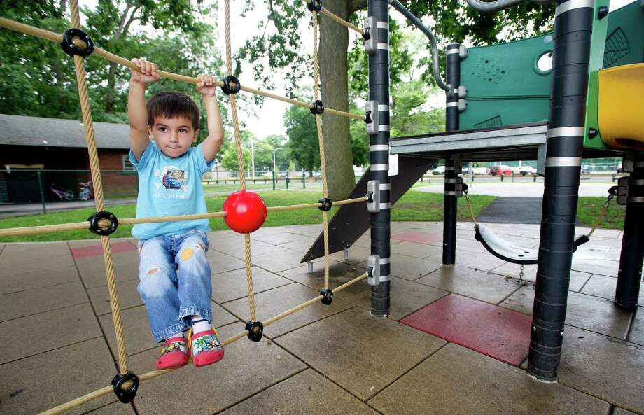 Max Villanueva, 3, plays at Scalzi Park after the ceremony for the completion of the park's renovation on Tuesday, July 2, 2013. Photo: Lindsay Perry / Stamford Advocate