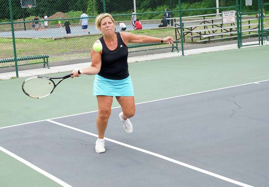 Jill Bakken plays tennis at Scalzi Park after the ceremony for the completion of the park's renovation on Tuesday, July 2, 2013. Photo: Lindsay Perry / Stamford Advocate