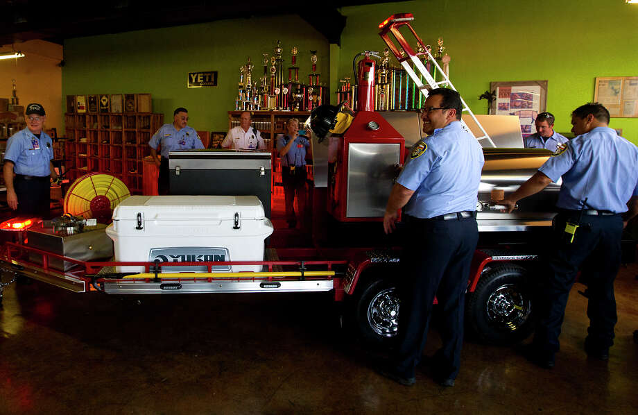 Firefighters look at a barbecue smoker donated by Pitts & Spitts BBQ, Tuesday, July 2, 2013, in Houston. Pitts & Spitts built the trailer with donations from local Houston vendors to raise money for the four families of the firefighters' that perished in the May 31 hotel fire. (Cody Duty / Houston Chronicle) /  2013 Houston Chronicle
