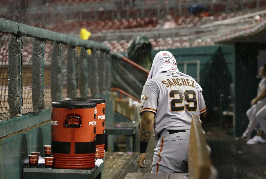 San Francisco Giants catcher Hector Sanchez prepares to leave the dugout in the bottom of the sixth inning of a baseball game against the Cincinnati Reds, Monday, July 1, 2013, in Cincinnati. The game was delayed by rain with Cincinnati leading 8-1.
