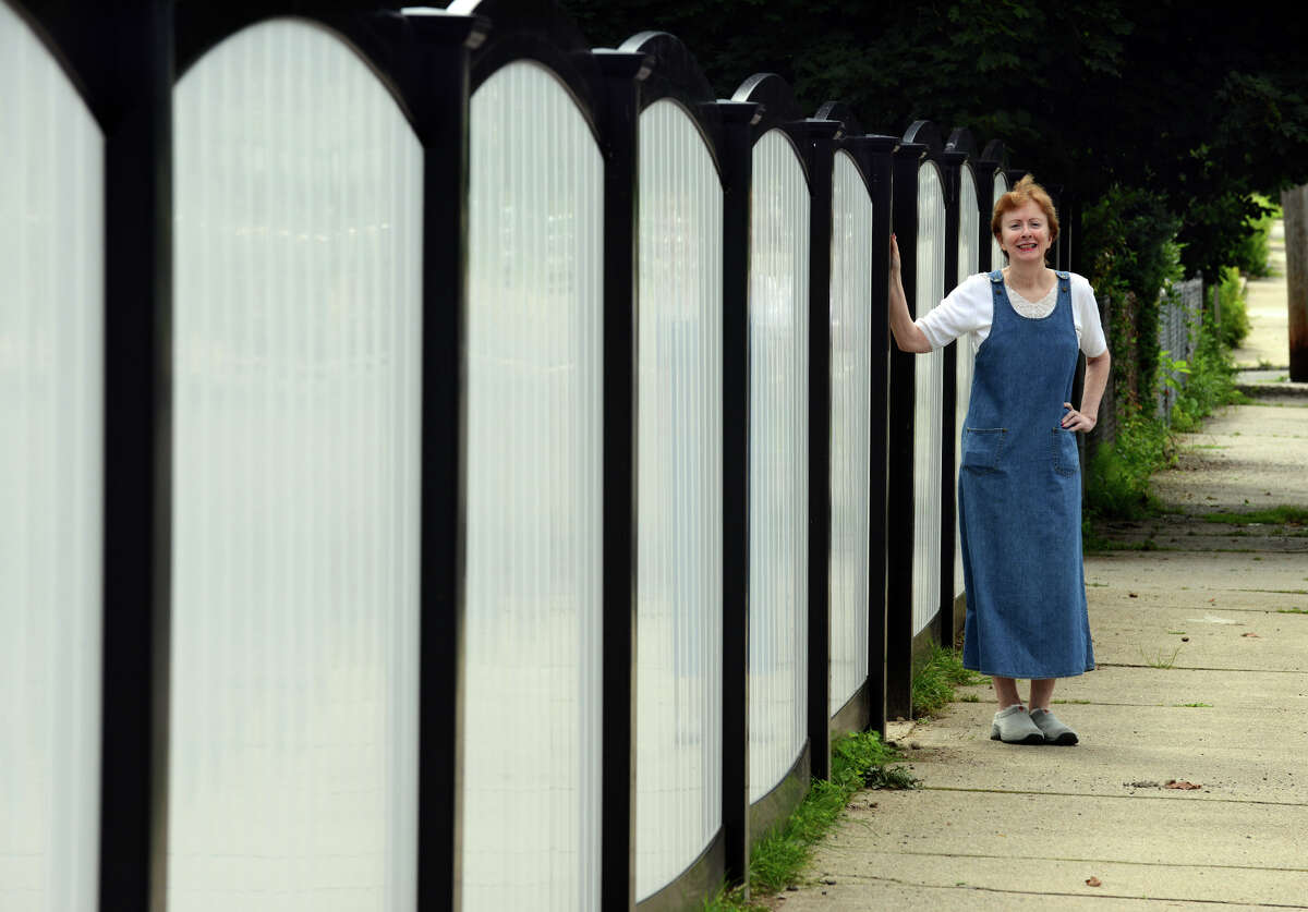 Wakelee Avenue resident Eileen Ryan poses next to a portion of new fence in front of her property in Ansonia, Conn. on Tuesday July 2, 2013. Ryan was replacing the fence after Superstorm Sandy but the town forced her to stop because it was supposedly a violation of city ordinance. On appeal it was overturned by the zoning board of appeals.