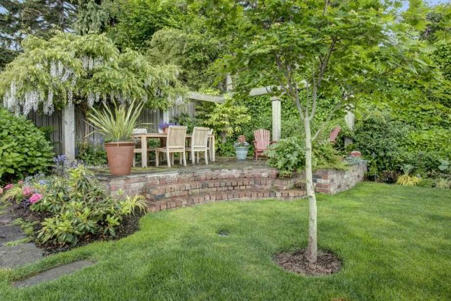 Bluestone patio, with arbor, of 2721 Warren Ave. N. The 2,730-square-foot brick house, built in 1929, has three bedrooms, 1.75 bathrooms, coved ceilings, and wood and tile floors on a 4,000-square-foot lot. It's listed for $799,000. Photo: Courtesy Bonnie Sanborn, Windermere Real Estate