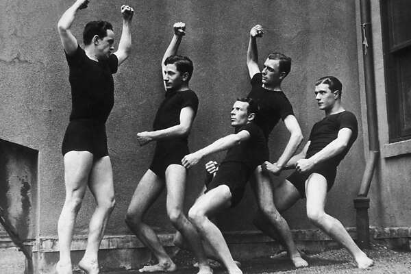 Full-length image of five men, dressed in matching black T-shirts and shorts, contorting their bodies while exercising, possibly on a rooftop, 1910s. The leader holds his stomach in and flexes his muscles while the others watch.