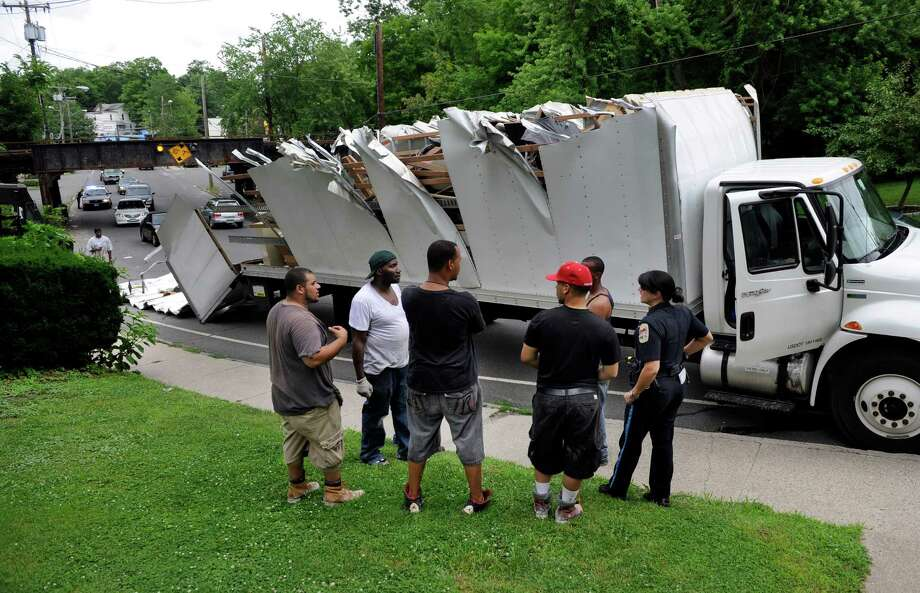 A moving truck too tall to make it under the West Street bridge had its top completely severed off  Tuesday afternnoon, July 2, 2013, in Danbury, Conn. Danbury Police Officer Regina Guss, right, speaks with those involved in the accident. Photo: Carol Kaliff / The News-Times