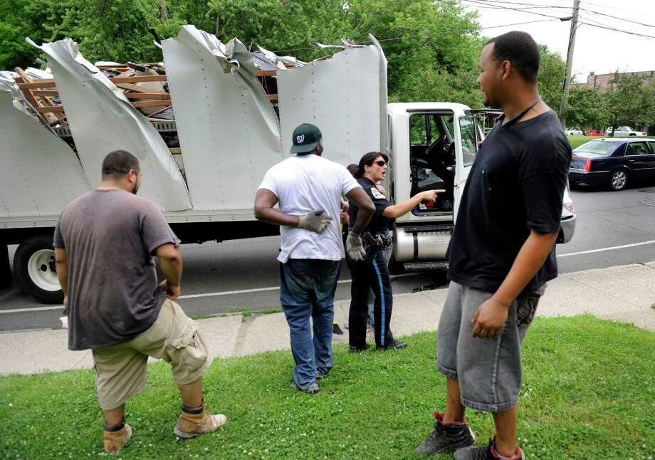 A moving truck too tall to make it under the West Street bridge had its top completely severed Tuesday afternnoon, July 2, 2013, in Danbury, Conn.  Danbury Police Officer Regina Guss, center, speaks with those involved. Photo: Carol Kaliff / The News-Times