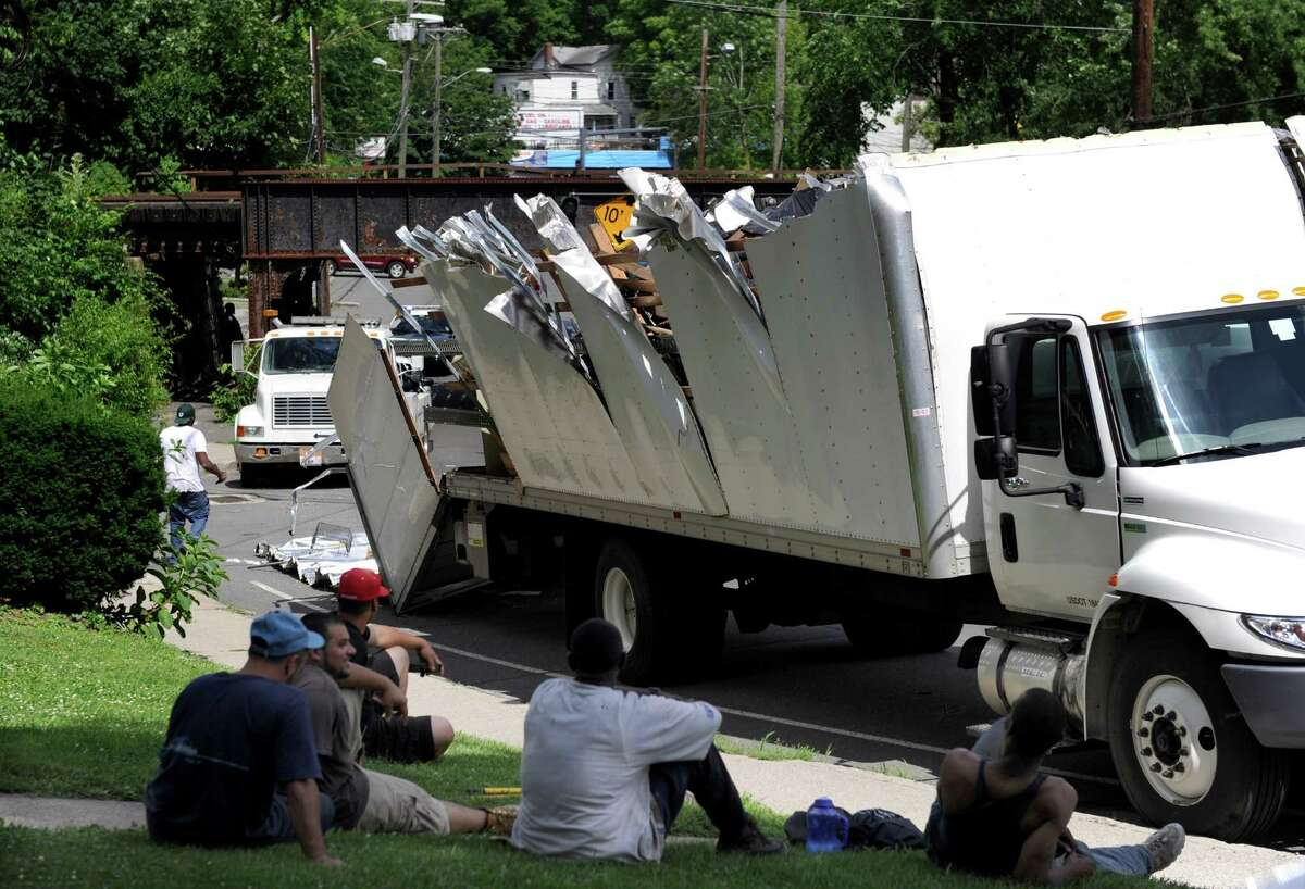 A moving truck too tall to make it under the West Street bridge had its top completely severed Tuesday afternnoon, July 2, 2013, in Danbury, Conn.