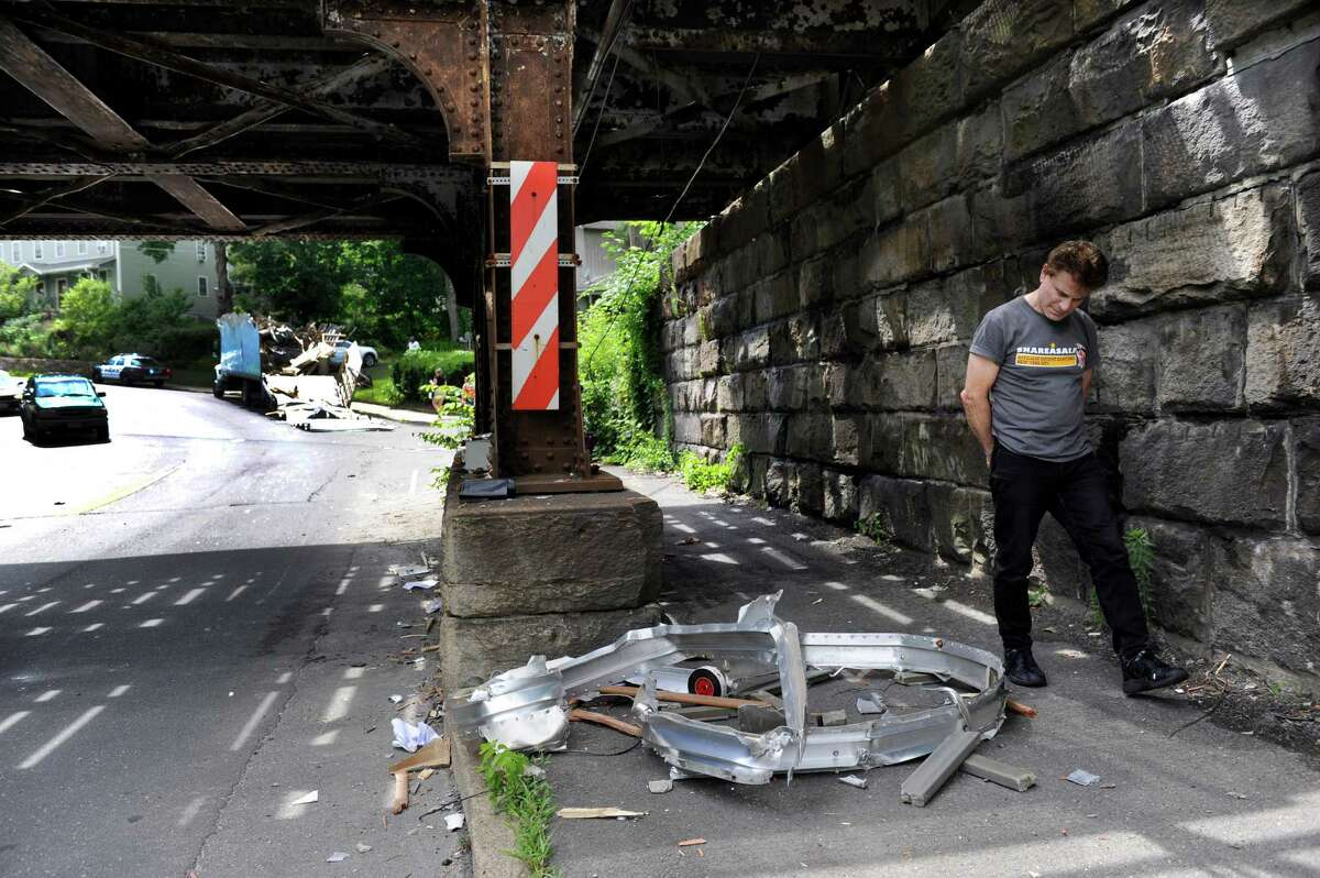 A passerby looks at damage to the West Street bridge when a moving truck too tall to make it under had its top completely severed Tuesday afternnoon, July 2, 2013, in Danbury, Conn.