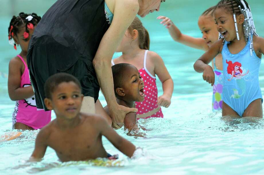 Neyco Braddock, center, swims with water safety instructor Susan Harder during a Learn-to-Swim class on Tuesday, July 2, 2013, at the Lincoln Park Pool in Albany, N.Y. Joining them are Lee-Sean Harvey, left, and Ariel Barcelo, far right. The children are with Club Fed Child Care Center, operated by Victory Child Care Inc. (Cindy Schultz / Times Union) Photo: Cindy Schultz / 00022972A
