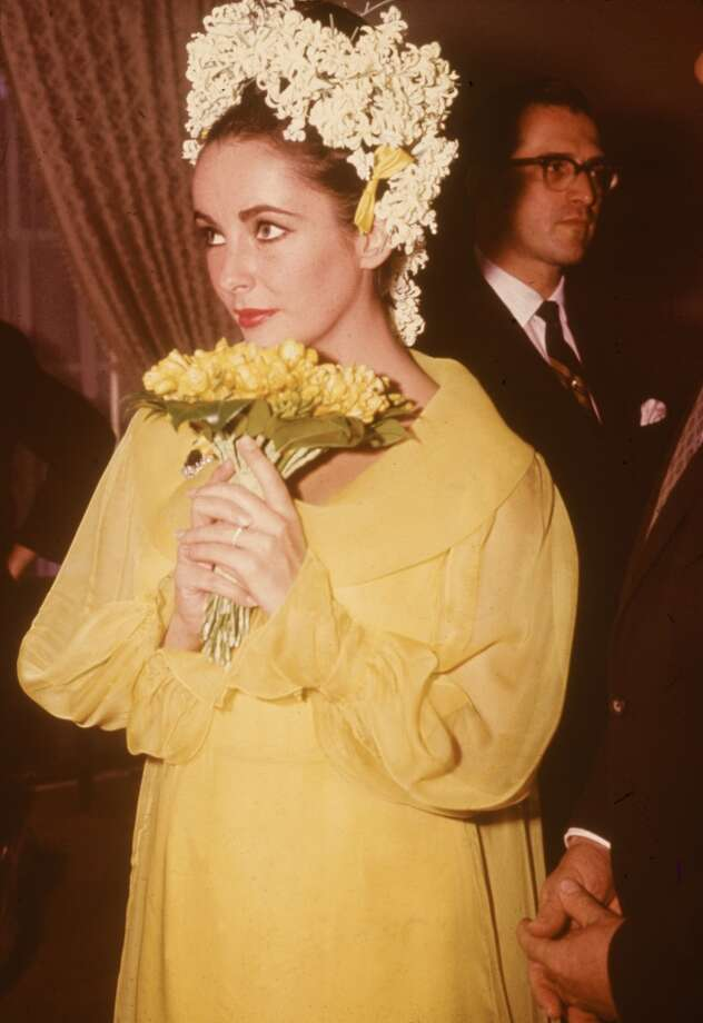 British-born actor Elizabeth Taylor, in a yellow dress and floral headdress, holds a bouquet of flowers at her wedding to actor Richard Burton, March 15, 1964. (Photo by Hulton Archive/Getty Images)