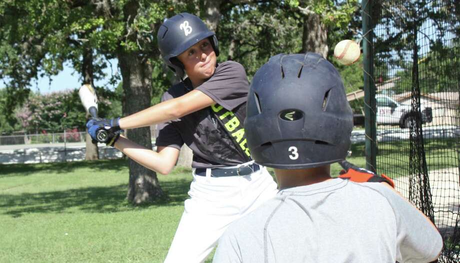 Kendall Elementary sixth-grader Caleb Ratcliffe draws a bead on a tossed ball during a hitting drill designed to improve players' swings at last week's Boerne ISD baseball camp. Photo: Mike Reeder / For The Northwest Weely