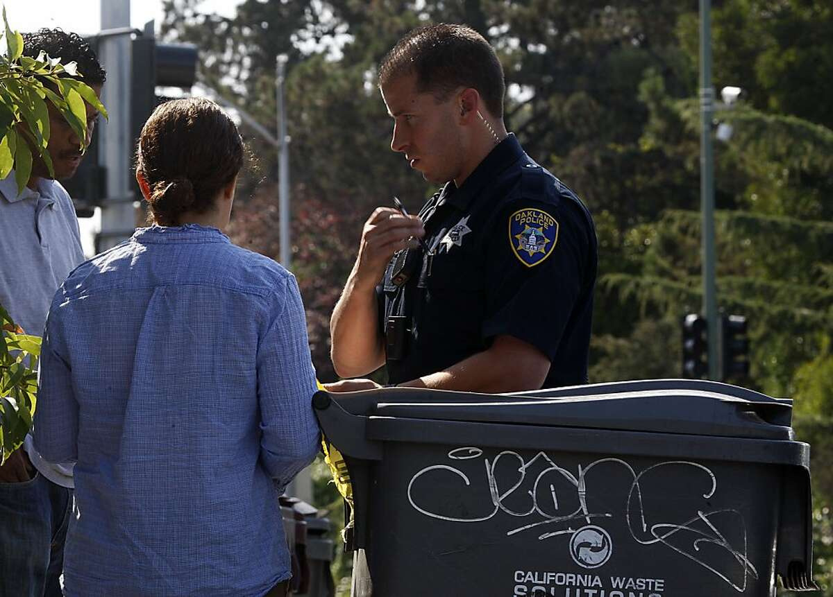 An Oakland officer talks with pedestrians the morning after two employees died from gunshot wounds at Wing Stop restaurant in Oakland.