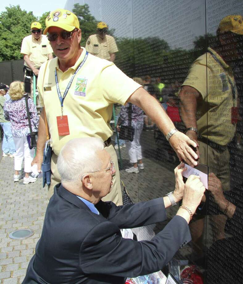 Leon Franklin kneels to create a rubbing of his brother's name from the Vietnam Veterans Memorial — The Wall — on Memorial Day. Photo: Courtesy Photo