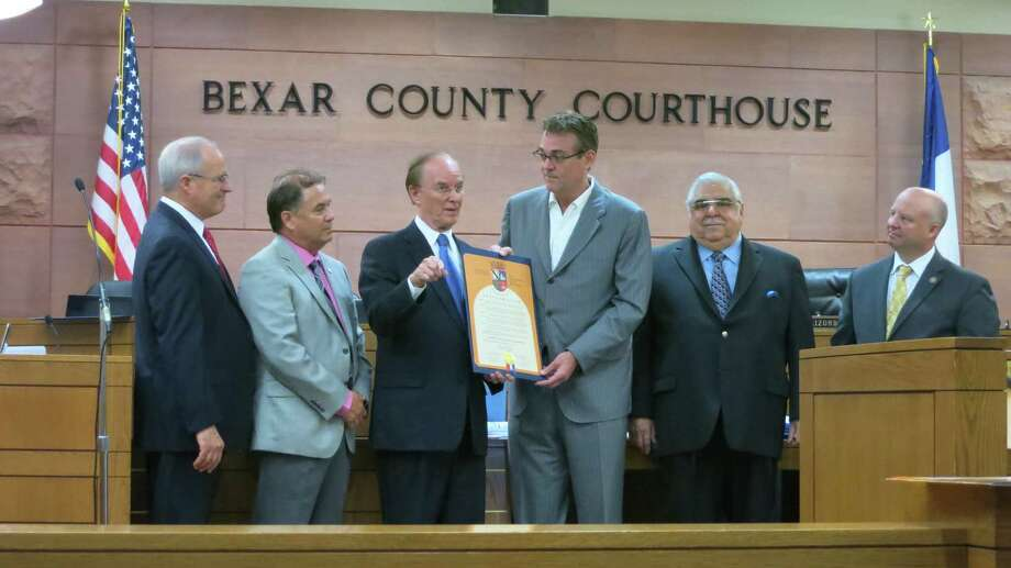 San Antonio Spurs General Manager R.C. Buford towers over members of Bexar County Commissioners Court on Tuesday, July 2, 2013, while receiving a county proclamation honoring the Spurs' outstanding NBA season. Photo: John W. Gonzalez / San Antonio Express-News