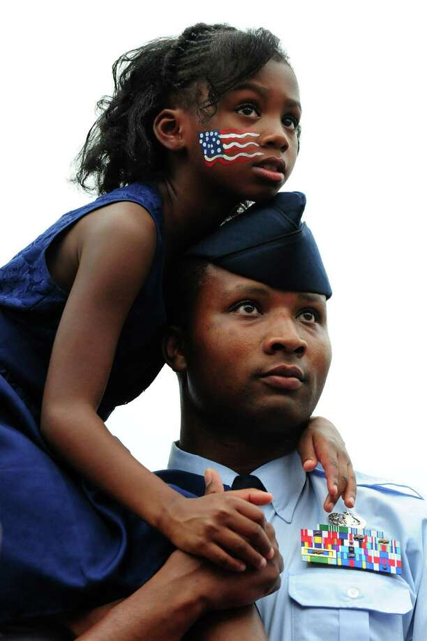 2011 -- Air Force Tech. Sgt. Marquis Mullins and his daughter Anya listen as President Barack Obama delivers remarks at an Independence Day barbeque for members of the armed services. Photo: Pool, Getty Images / 2011 Getty Images