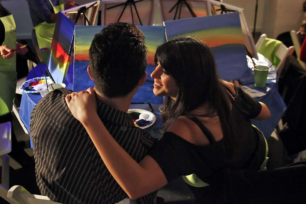 Arya Mortazavi gets a kiss from his girlfriend Sarvey Alibeigi during Paint Nite at Temple Bar in San Francisco, Calif., on Tuesday, June 24, 2013. Paint Nite is a new social painting phenomenon in which an artist teaches people how to paint a specific scene while everyone socializes in a bar or club.