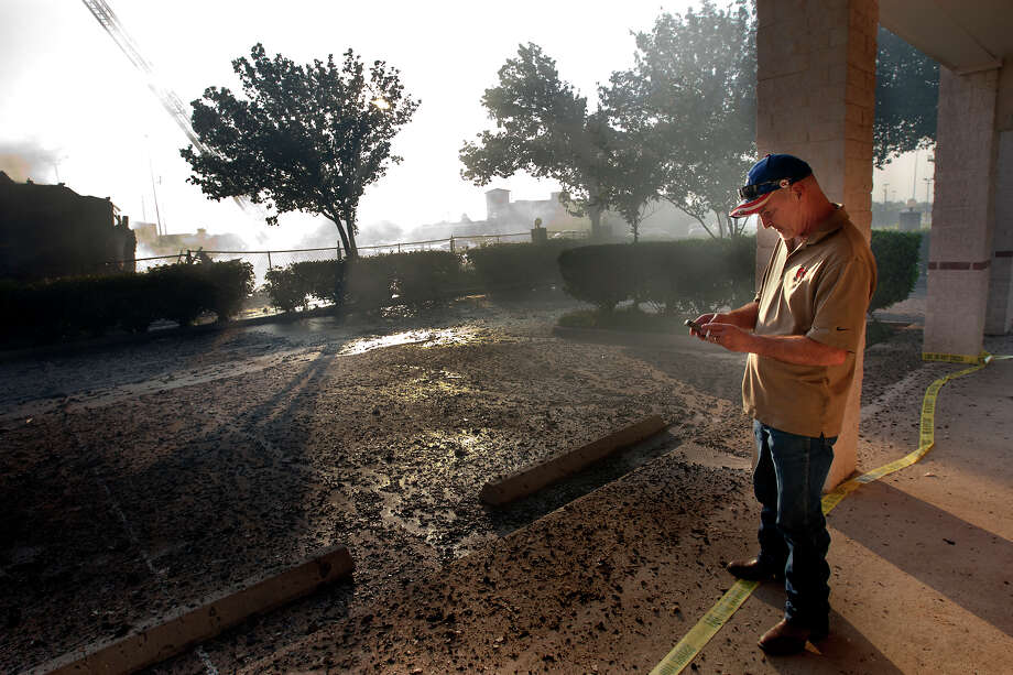 Mike Roberts looks at his phone after taking a picture of a 4-alarm blaze that started in a motel under construction along Hempstead Highway near FM 1960, Tuesday, July 2, 2013, in Houston. Photo: Cody Duty, Houston Chronicle / © 2013 Houston Chronicle
