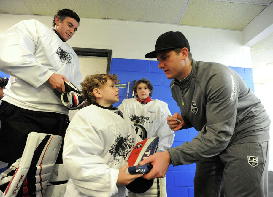 Jonathan Quick signs autographs for Theron Case, 6, as his brother, Samuel, 8, and his father, Richard, look on after the NHL's Jonathan Quick Goalie Camp at Stamford Twin Rinks on Tuesday, July 2, 2013. Quick is a goalie for the LA Kings. Photo: Jason Rearick / Stamford Advocate