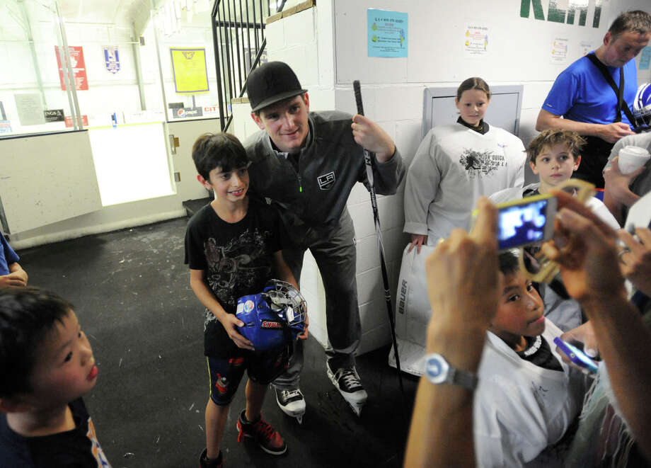 Ari Silverstein, 9, gets his photograph taken with LA Kings goalie Jonathan Quick after the NHL's Jonathan Quick Goalie Camp at Stamford Twin Rinks on Tuesday, July 2, 2013. Photo: Jason Rearick / Stamford Advocate