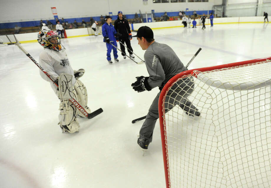 Jonathan Quick demonstrates a technique for Cameron Smith, 11, during the NHL's Jonathan Quick Goalie Camp at Stamford Twin Rinks on Tuesday, July 2, 2013. Photo: Jason Rearick / Stamford Advocate