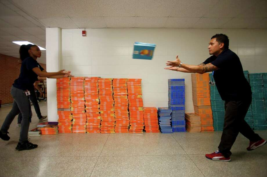 Morgan Goff, left, and Bobby Espinosa move textbooks as HISD takes over North Forest ISD's Fonwood Elementary School, July 2, 2013 in Houston.   Read more here. Photo: Eric Kayne, For The Chronicle / ©2013 Eric Kayne
