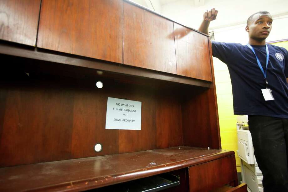HISD worker Patrick Johnson stands ready to move a desk out of the front office as HISD takes over North Forest ISD's Fonwood Elementary School, July 2, 2013 in Houston. Photo: Eric Kayne, For The Chronicle / ©2013 Eric Kayne