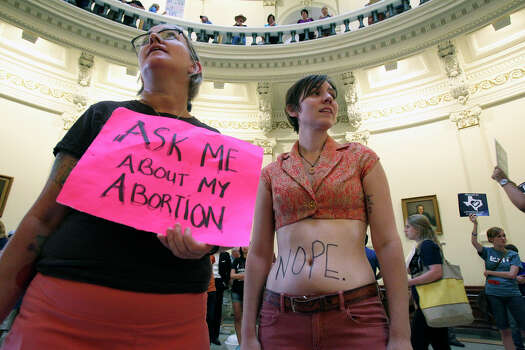 Spike Gillespie (left) and Margaret Halpin stand in the rotunda as demonstrators voice their opinion as the Capitol building fills before the Senate debates passage of abortion legislation on July 12, 2013. Photo: Tom Reel, San Antonio Express-News