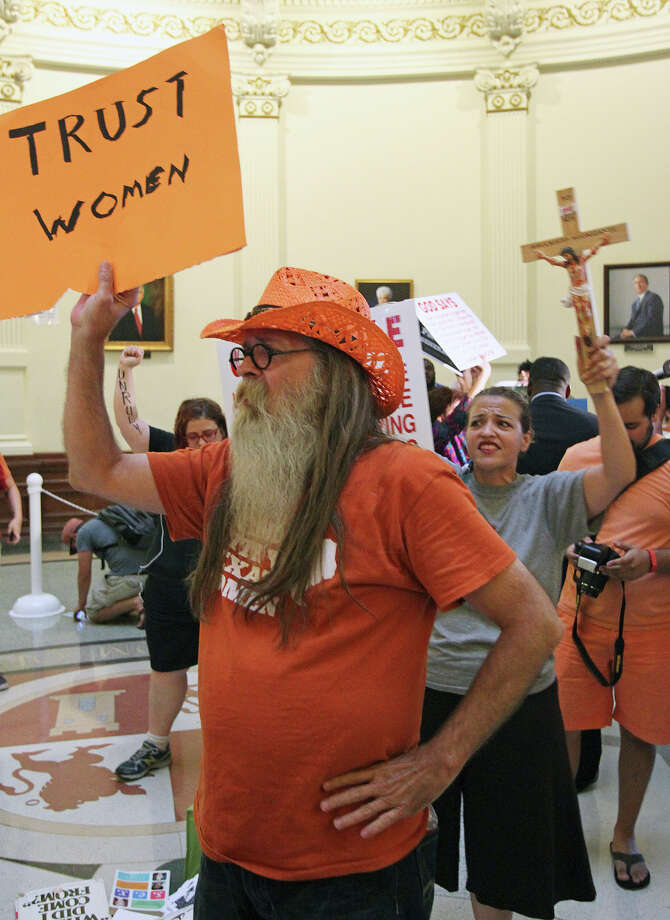 Mark Clinto holds his sign in the rotunda as demonstrators voice their opinion as the Capitol building fills before the Senate debates passage of abortion legislation on July 12, 2013. Photo: Tom Reel, San Antonio Express-News